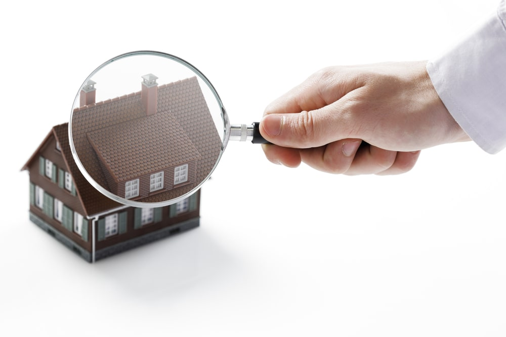 Hand holding magnifying glass over a house
