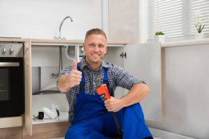 Plumber With Adjustable Wrench In Kitchen Room