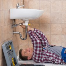 San Antonio Plumber Lying On Floor Fixing Sink