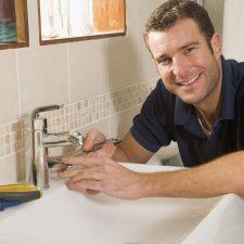 Smiling plumber fixing sink in San Antonio
