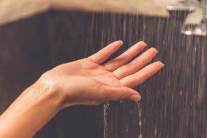woman's hand under water in shower